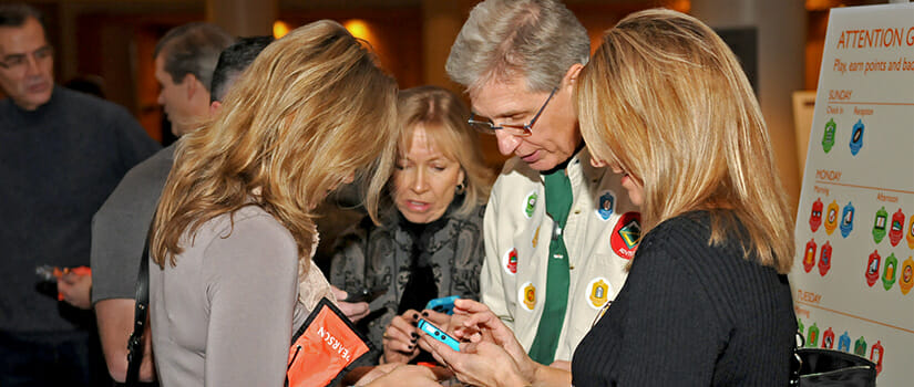 Attendees engaging with gamification platform utilizing conference app sponsorship