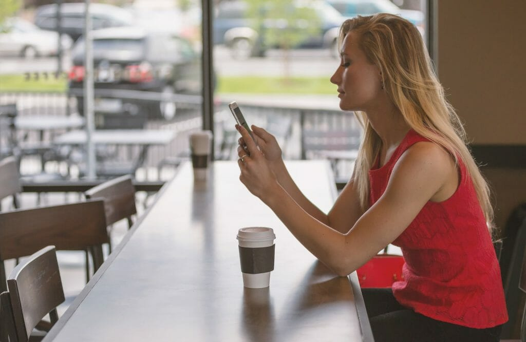 Woman creating event survey questions at coffee shop